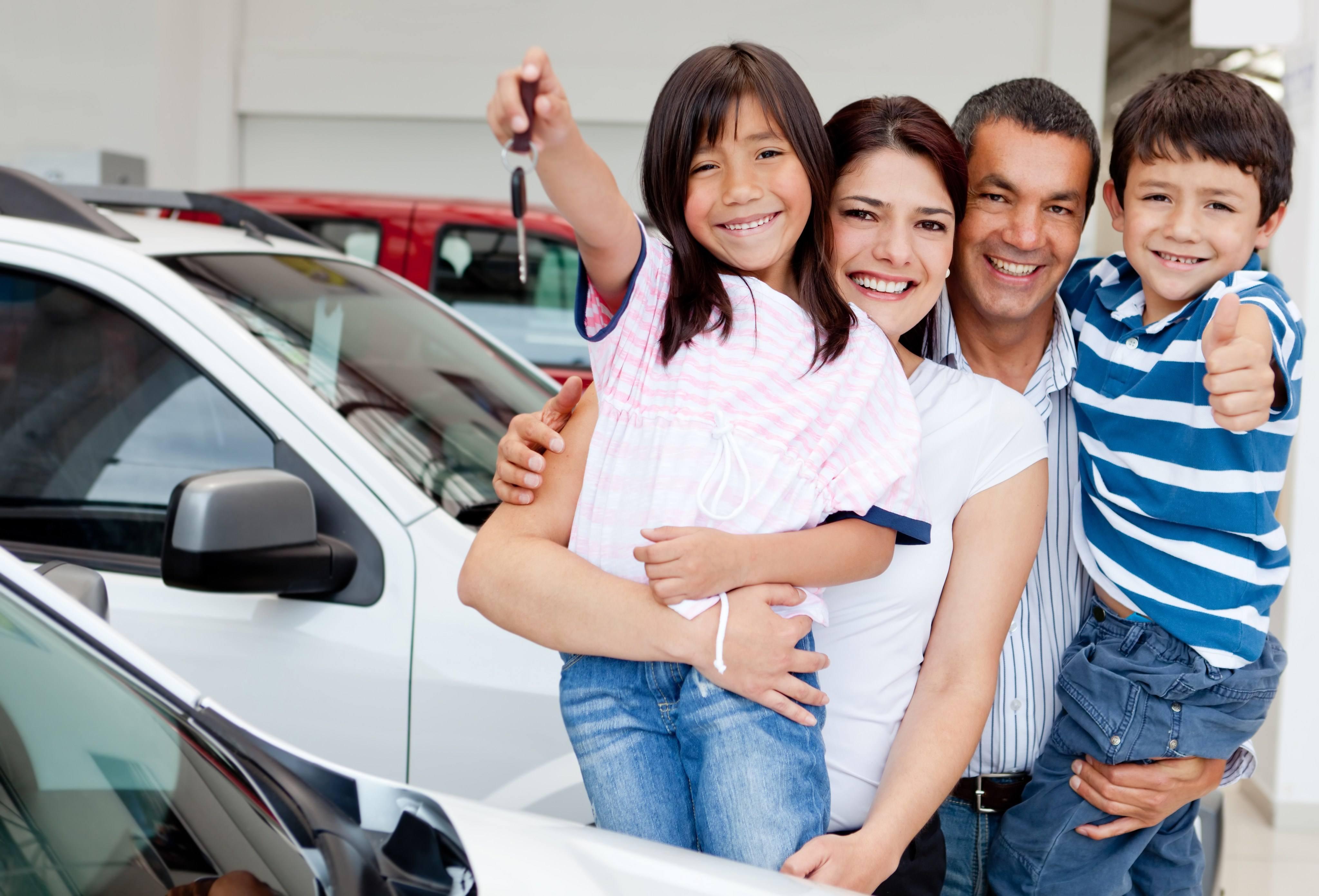 Happy family holding keys to new car