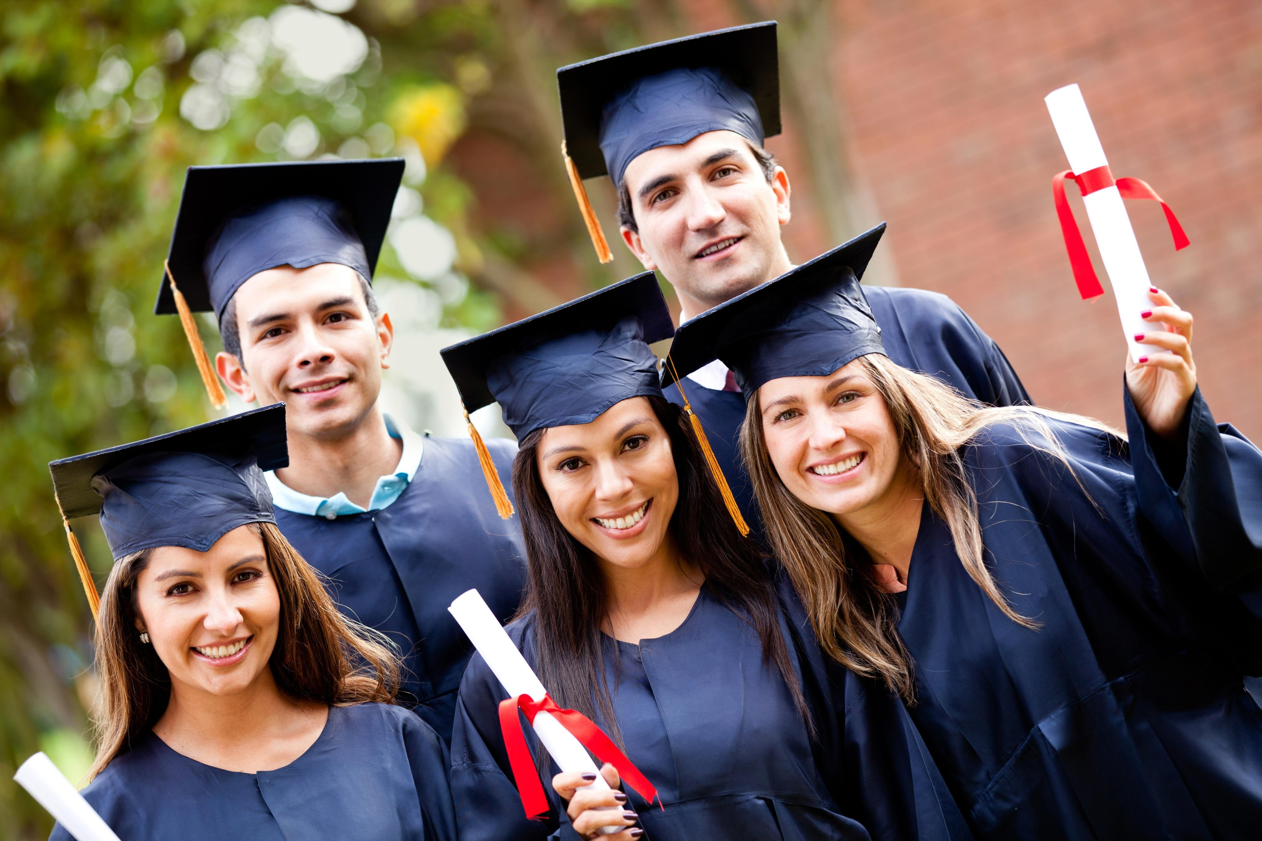 Group of graduate students holding their diploma after graduation
