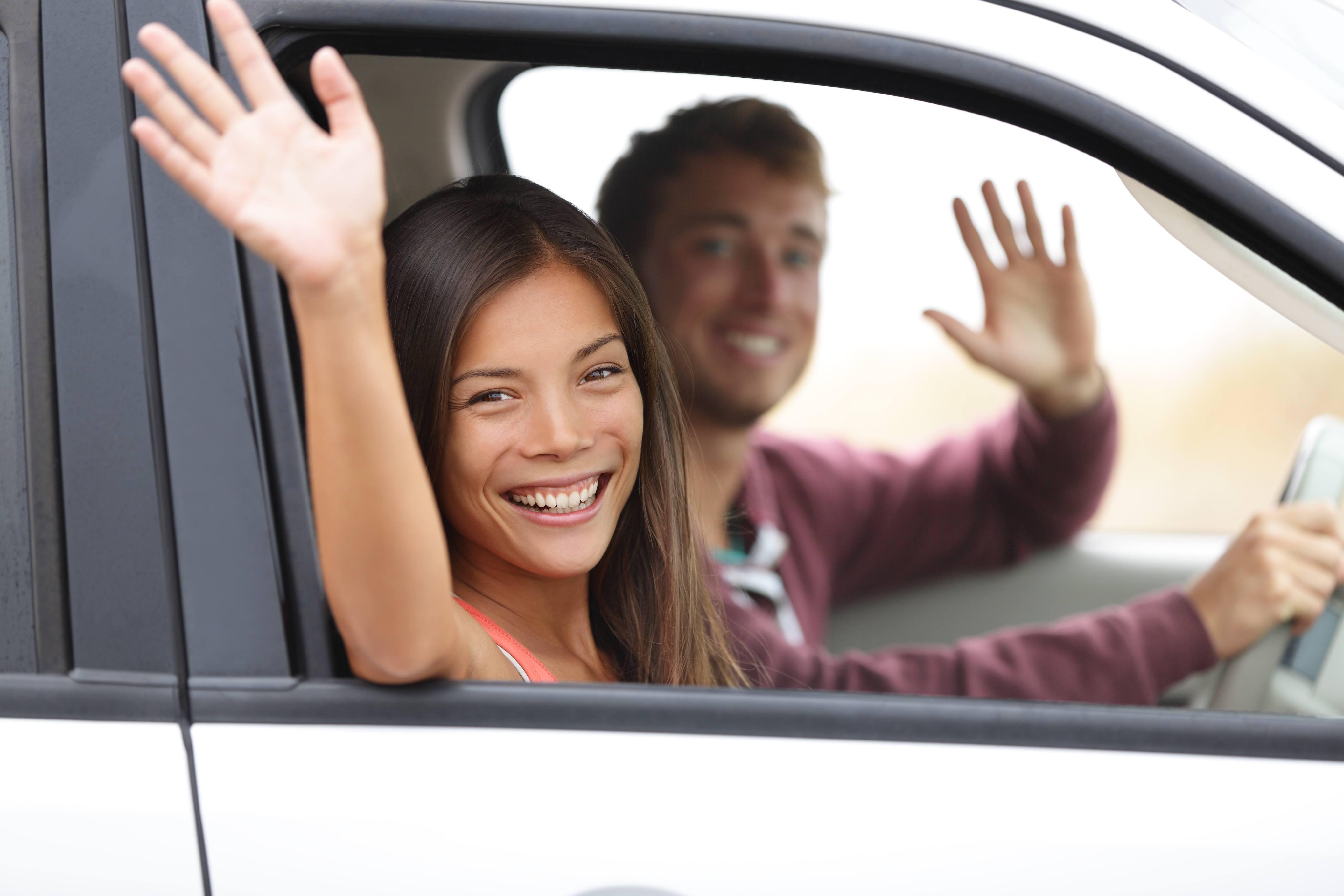 Happy couple in car waving